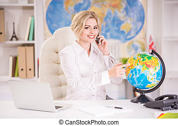 Travel agency - Beautiful travel agent sitting at the table...