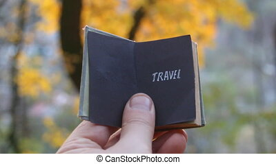 Travel agency idea. - Hand holding a book with text travel