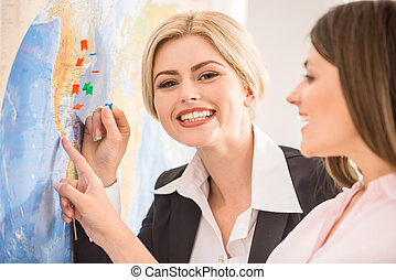 Travel agency - Beautiful women standing near map with...