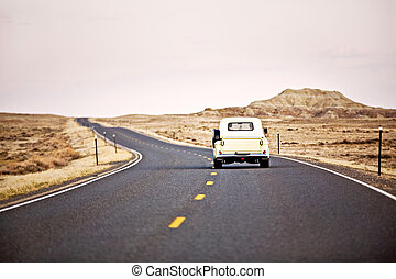 travel America - vintage car driving down highway in Wyoming...