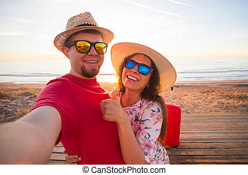 Travel and holidays concept - Happy young couple in love takes selfie portrait on the beach