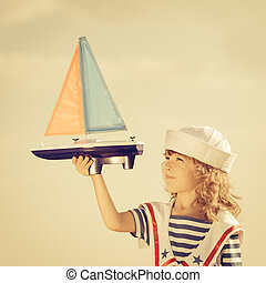 Travel and vacations concept - Happy kid playing with toy...