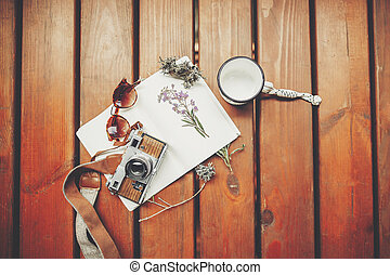 travel and wanderlust concept. map with sunglasses, photo camera, mug, notebook and wildflowers herbs on wooden background, top view. stylish traveler hipster set flat lay