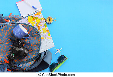 Travel background concept / Planning Essential vacation trip items in backpacks travel accessories with camera sunglasses compass map notebook and coffee cup for plane Traveler's on blue