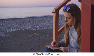 Travel: beautiful girl tourist drawing sunset at the beach....