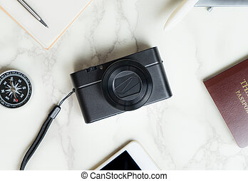 Travel blogger accessories on luxury white marble table with camera in the middle