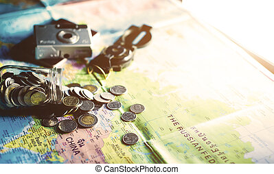 Travel budget concept. Travel money savings in a glass jar with compass, passport and camera background