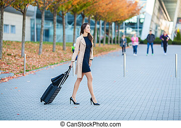 Travel. Business Woman in airport talking on the smartphone while walking with hand luggage in airport going to gate. Girl using mobile phone for conversation