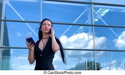 Travel. Business Woman in airport talking on the smartphone while walking with hand luggage in airport going to gate.