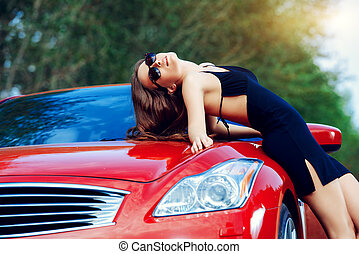 travel by car - Attractive young woman near the red sports...