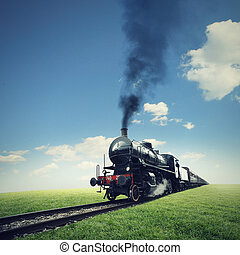 Travel by steam train - steam engine train crosses a green ...