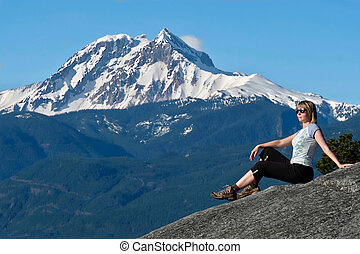Travel Canada. Woman on mountain cliff against snow capped peak.