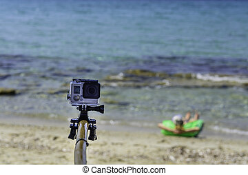 Travel concept - Action camera photography over sea view, with selfie Monopod