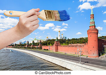paintbrush paints blue sky over Moscow Kremlin