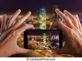 Travel concept. Hands making photo of night Batumi City,...