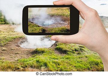tourist photographs geyser in Haukadalur - travel concept -...