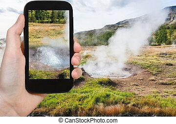 tourist photographs geyser pool in Haukadalur - travel...