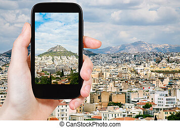 tourist taking photo of Athens city skyline