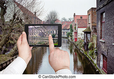 tourist taking photo of canal in Bruges