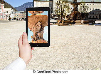 tourist taking photo of fountain in Salzburg