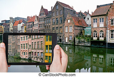 tourist taking photo of old houses in Ghent
