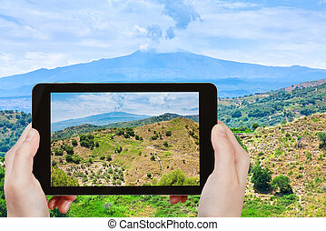 travel concept - tourist taking photo of rural landscape with Etna mount in Sicily on mobile gadget, Italy