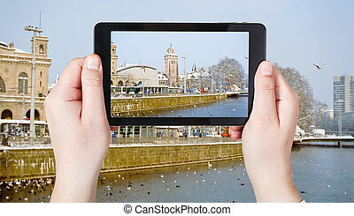 tourist taking photo of waterfront in Zurich