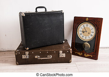 Travel concept. Vintage retro wall clock and old classic leather suitcase on a woodem floor. Travel, time concept