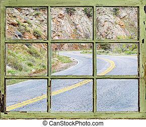 travel concept - windy road through old window
