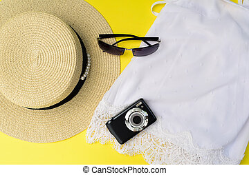Travel concept with top, straw hat, sunglass, camera.