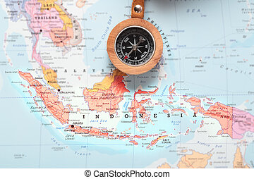 Compass on a map pointing at Indonesia and planning a travel destination