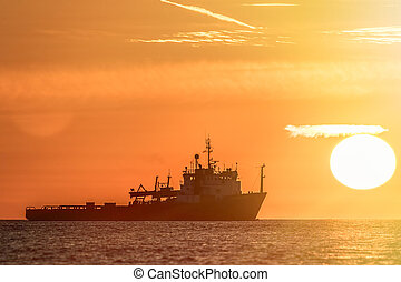 Travel destination. Sun haze over a tropical ocean at sunrise. Fishing boat silhouette infront of a glowing sun.