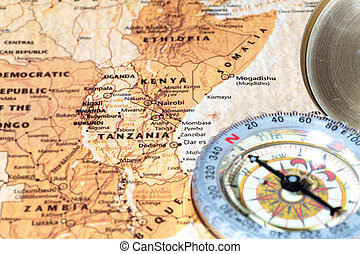 Compass on a map pointing at Tanzania and Kenya, planning a travel destination