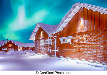 Travel Destinations Concepts. Beautiful Multicoloured Vibrant Aurora Borealis known as Northern Lights Playing with Vivid Colors Over Traditional Lapland Houses in Finland.