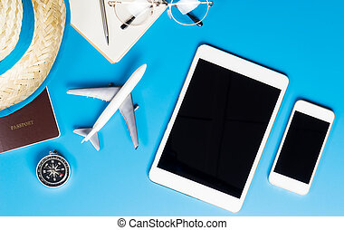 Travel equipments with Blank tablet and phone screen on blue.
