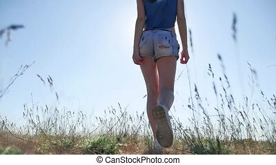 travel. Girl Young woman arms raised enjoying the fresh air in grass nature sunlight