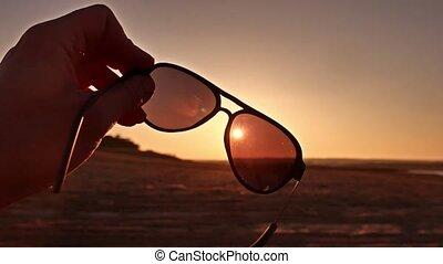 travel. Hand holds sunglasses at sunset lifestyle nature -...