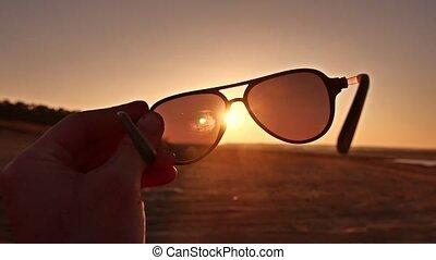 travel. Hand holds sunglasses at sunset nature lifestyle -...