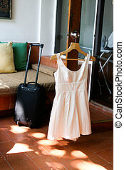 Dress and suitcase with an iron in the background - travel and tourism.