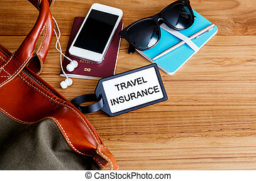 Travel insurance tag with bag on wood background