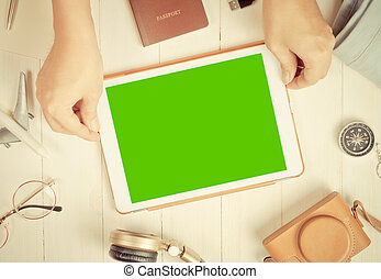 Travel is holding blank tablet screen on a table full of travel accessories