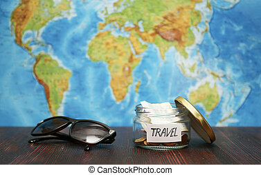 Travel money in jar, sunglasses, world map at background.