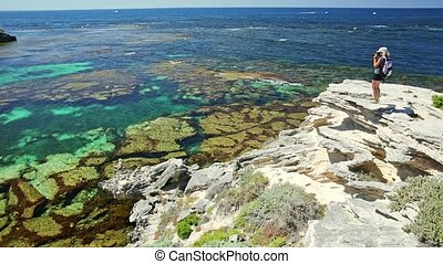 Western Australia travel discovery concept. Travel photographer on rocks at Jeannies Lookout, Rottnest Island, Western Australia. Female with professional camera in popular tropical island near perth.
