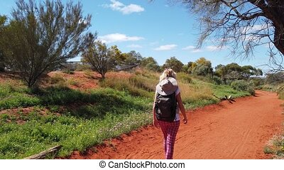 Travel photographer walking along red sand at Desert Park at Alice Springs near Mac Donnell Ranges. Photography in the Northern Territory, Central Australia.
