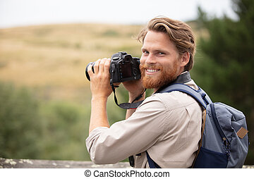 travel photographer man taking nature video of mountain landscape
