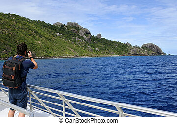 Travel photographer photographing the landscape of a tropical island