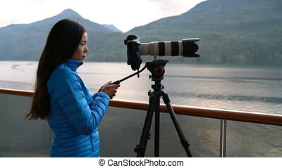 Travel photographer with professional telephoto lens camera ...