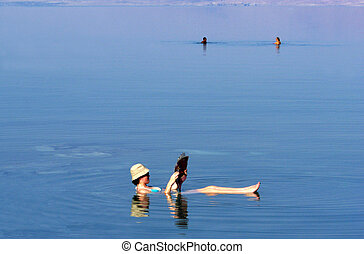 A young woman floating while reading a magazine at the Dead Sea, Israel.