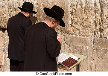 Jewish Men are praying at the western wall in the old city in Jerusalem, Israel.
