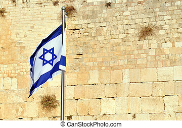 The Israeli National Flag against the Kotel Wailing Western Wall empty at night in Jerusalem, Israel.